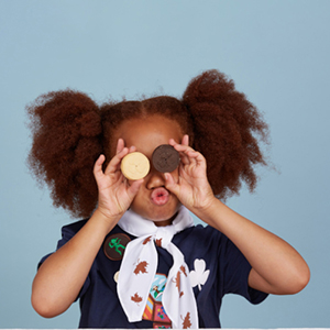 girl covering eyes playfully with cookies
